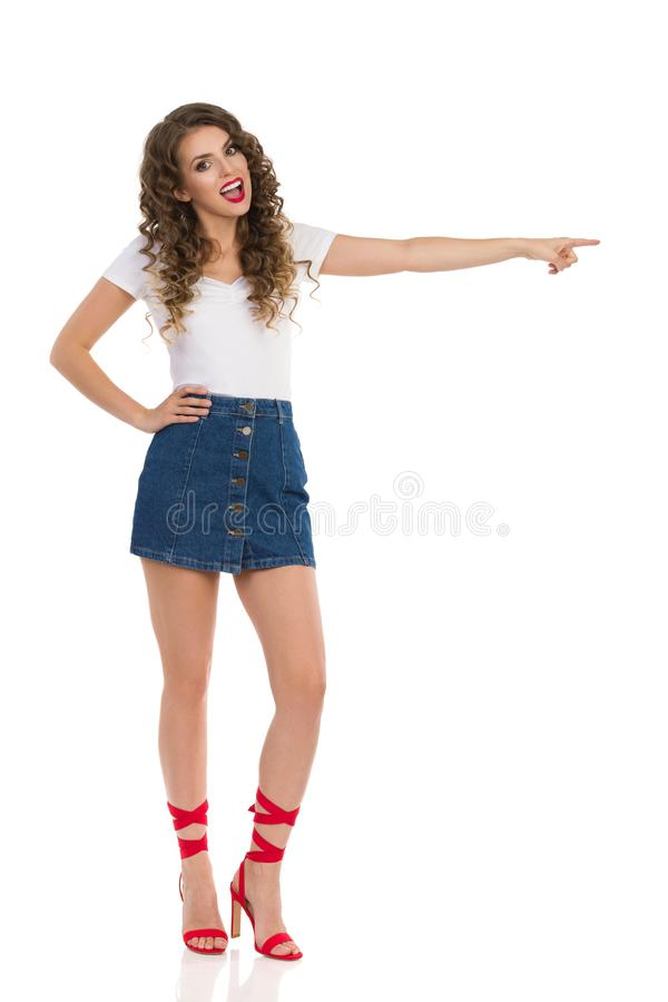 Young Woman In Jeans Mini Skirt And Red High Heels Is Pointing And Talking. Beautiful young woman in jeans mini skirt, white top and red high heels is pointing stock image