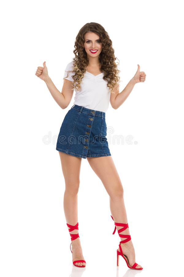 Young Woman In Jeans Mini Skirt And Red High Heels Is Standing And Showing Thumbs Up. Beautiful young woman in jeans mini skirt, white top and red high heels is royalty free stock photography