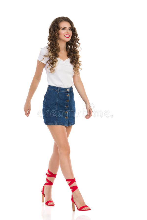 Young Woman In Jeans Mini Skirt And Red High Heels Is Walking And Looking Away. Confident young woman in jeans mini skirt, white top and red high heels is royalty free stock photography