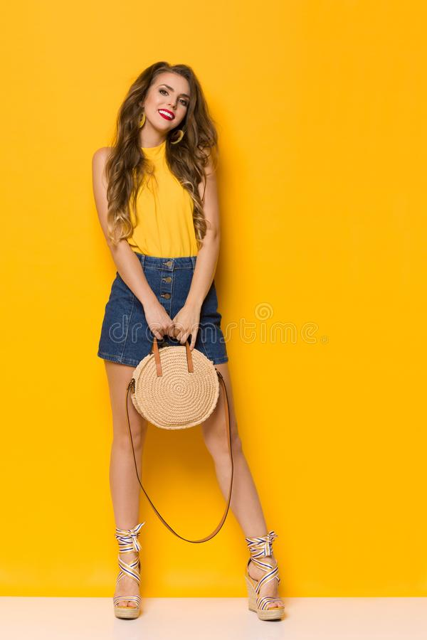 Young Woman In Jeans Mini Skirt And Wedges Holding Braided Straw Round Purse. Beautiful young woman in jeans mini skirt, wegdes and yellow top is holding braided stock image