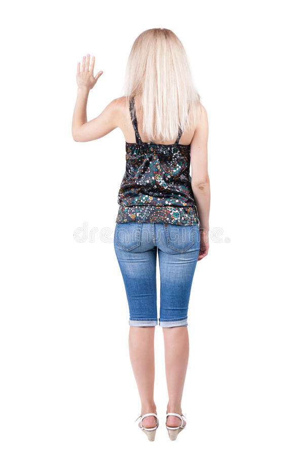 Young woman in jeans presses down on something. royalty free stock image