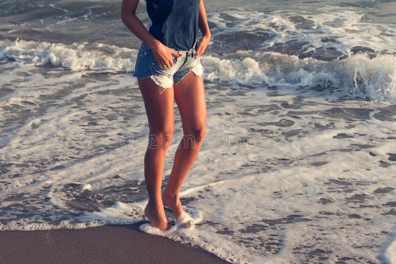 Young woman in jeans shorts walking through sea water at sunset sandy beach summer stock photography