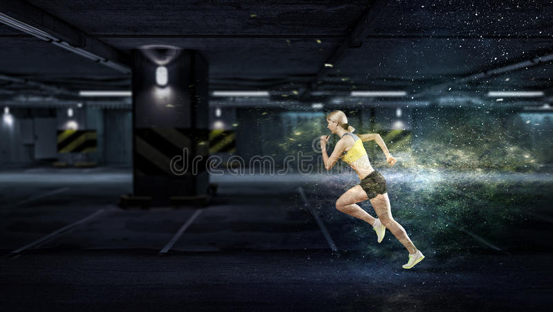 Young woman jogger. Young woman athlete in underground parking running fast stock photography