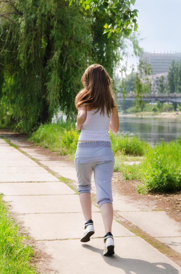 Download Young Woman Jogging Alongside A River Stock Photo - Image: 25430914