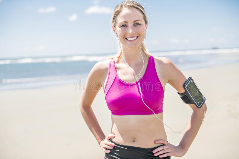 Young woman jogging on the beach in summer day. Athlete runner exercising actively in sunny day royalty free stock photo