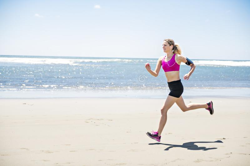 Young woman jogging on the beach in summer day. Athlete runner exercising actively in sunny day royalty free stock photography