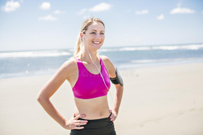 Young woman jogging on the beach in summer day. Athlete runner exercising actively in sunny day royalty free stock image