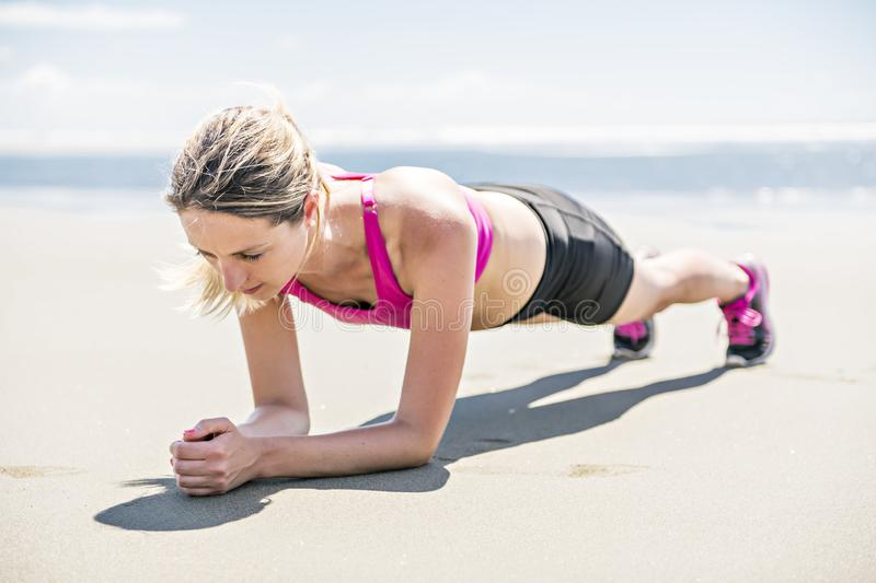 Young woman jogging on the beach in summer day. Athlete runner exercising actively in sunny day stock photos