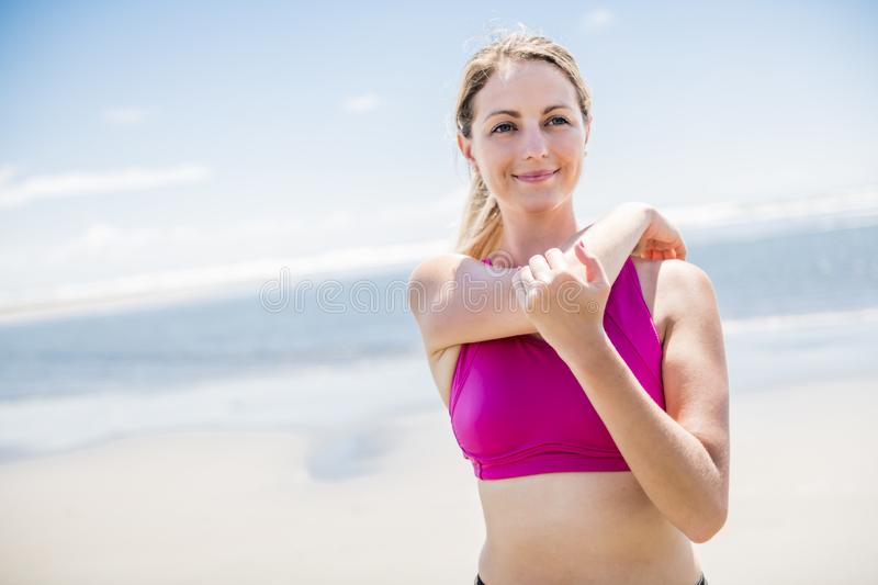 Young woman jogging on the beach in summer day. Athlete runner exercising actively in sunny day royalty free stock photos