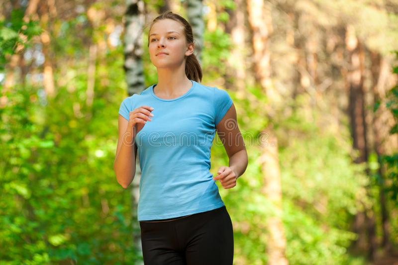 Young woman jogging in park royalty free stock photography