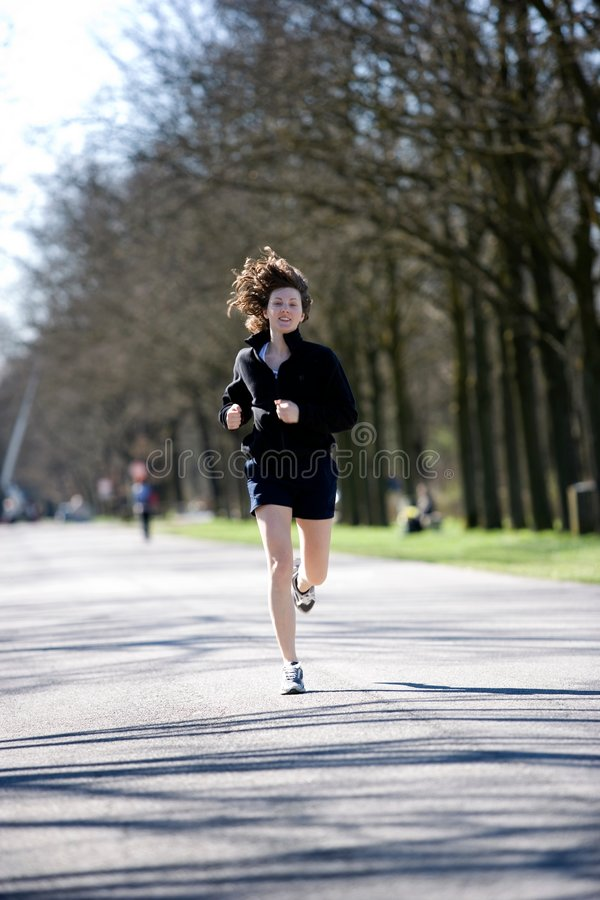 Young woman during jogging in a park. Jogging during late winner,in the first sunny days of the nex spring royalty free stock photography