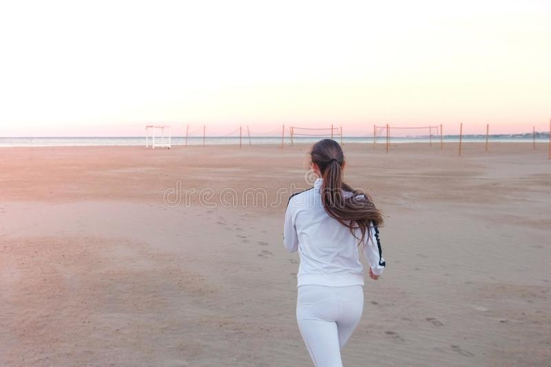 Young woman is jogging on the sand beach by the sea at sunrise in autumn, back view. stock photos