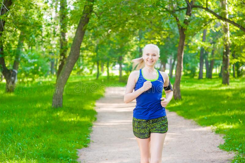 Young woman jogging in summer park and listening to music using smart phone royalty free stock image