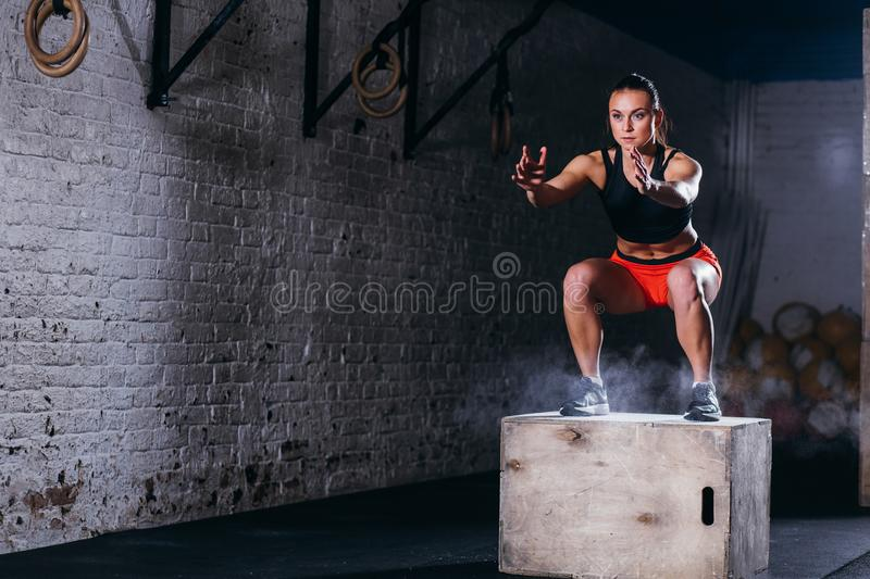 Woman jumping box. Fitness woman doing box jump workout at cross fit gym. Young woman jumping box and talc powder departs from under feet. Fitness woman doing royalty free stock image