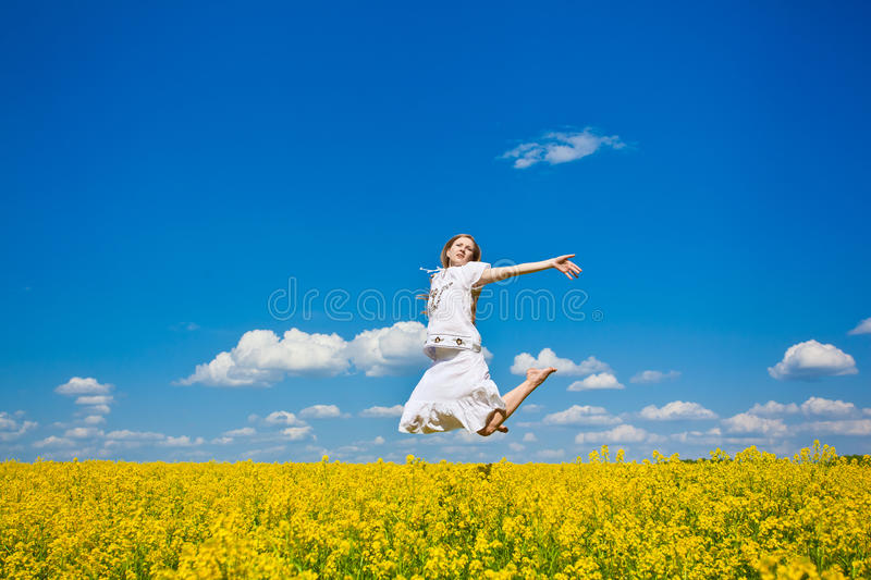 Young woman jumping on field royalty free stock photo