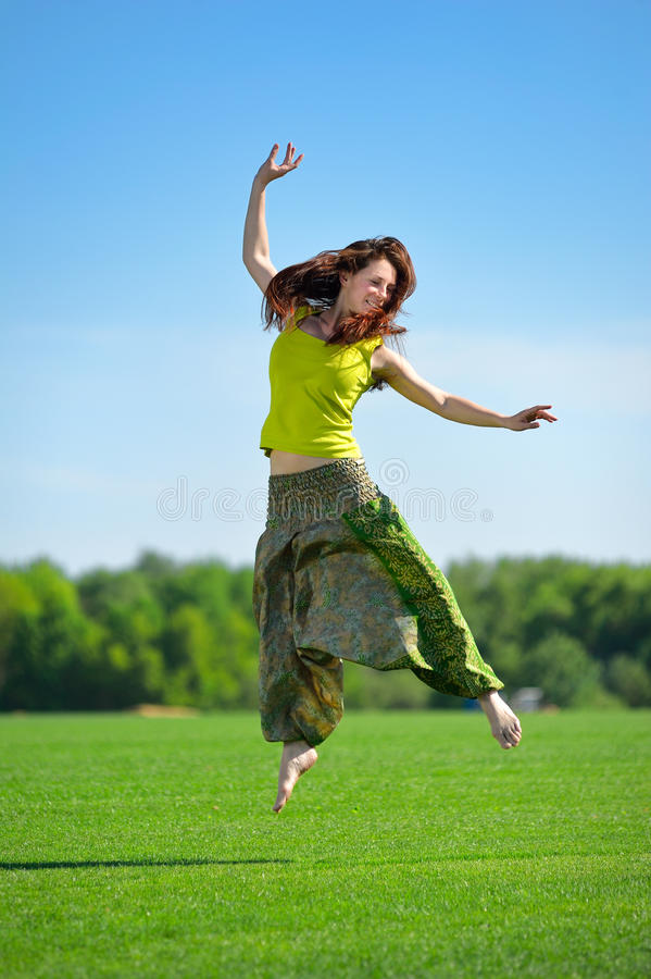 Young woman jumping on a green meadow stock photo
