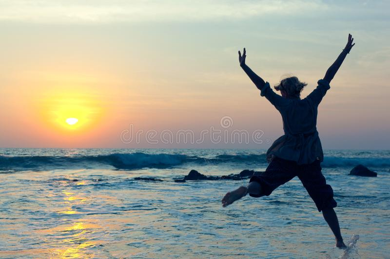 Young woman jumping with joy over the water royalty free stock photos