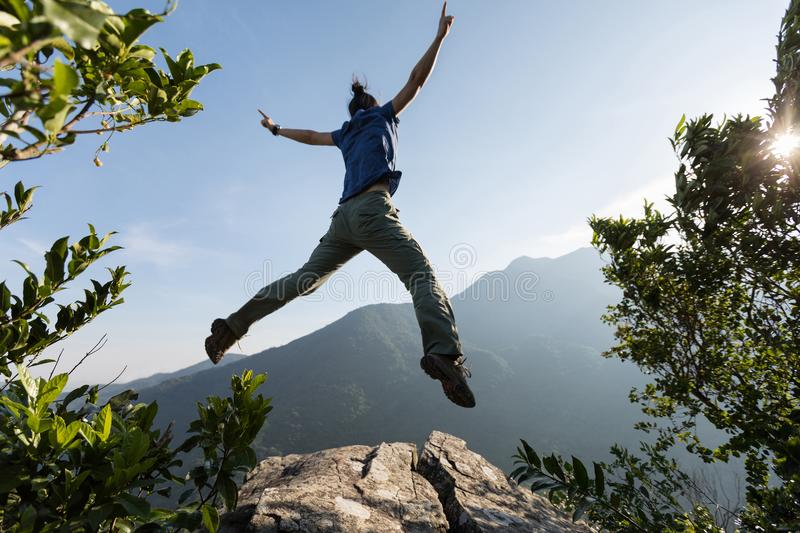 Young woman jumping on mountain peak royalty free stock photo