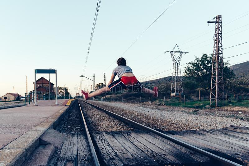 Young woman is jumping on the railroad tracks at old railroad st royalty free stock photography