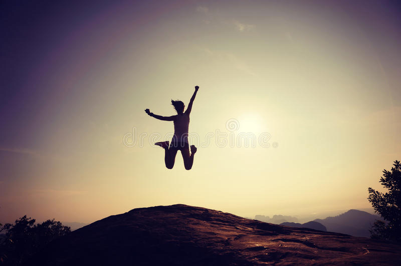 Woman jumping on rocky mountain peak face the sunrise. Young woman jumping on rocky mountain peak face the sunrise stock photo