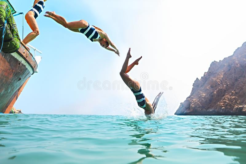 Young woman jumping from a sailing boat stock photos