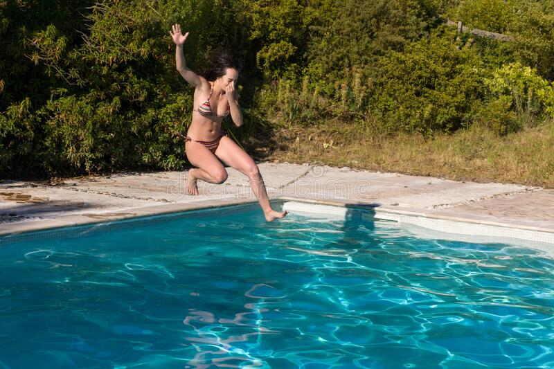 Young woman jumping into the swimming pool almost in the water royalty free stock photo
