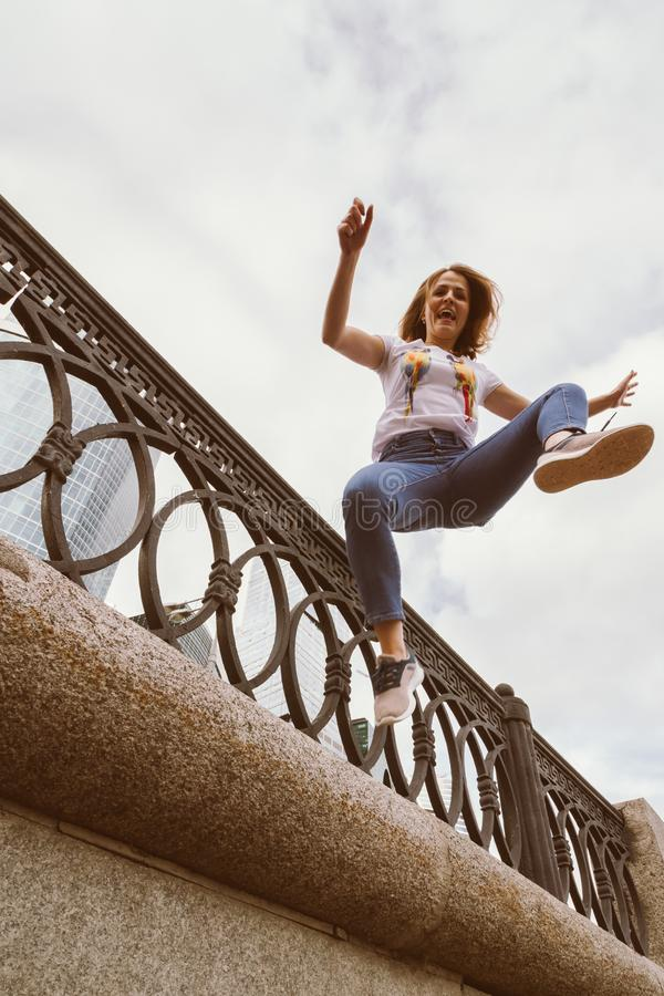Young woman jumping on the waterfront with outstretched arms to the sides royalty free stock image