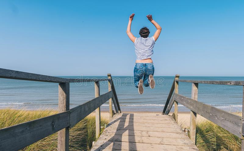 Young Woman Jumps on Beach over a wooden path to the Baltic sea stock photo
