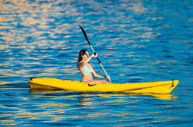 Young woman in a kanu kayak exercising in the ocean royalty free stock photos