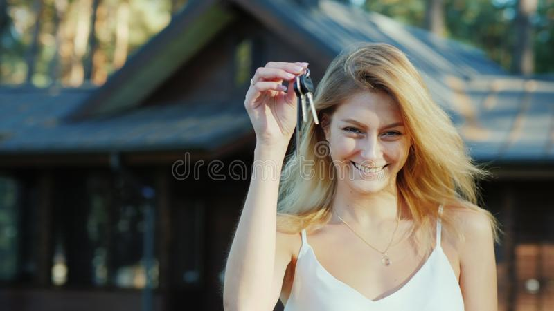 Young woman with keys from home. Smiling, looking at the camera. New wooden cottage in the background. Young woman with keys from home. Smiling, looking at the royalty free stock photo