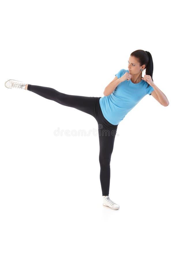 Young woman kick-boxing stock image