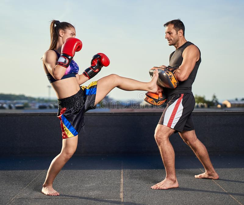 Young woman kickboxer in urban environment, training. Young women kickbox fighter training with her coach on the roof above the city royalty free stock photos