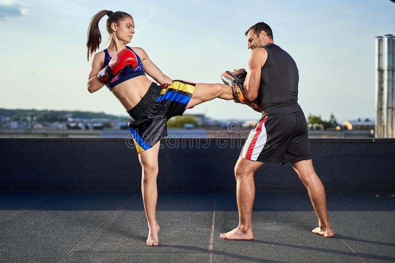 Young woman kickboxer in urban environment, training stock image
