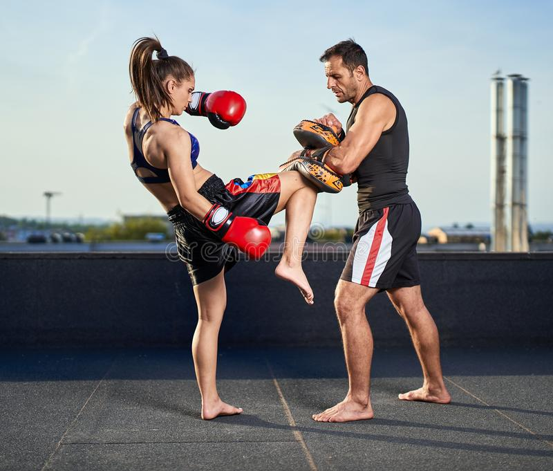 Young woman kickboxer in urban environment, training. Young women kickbox fighter training with her coach on the roof above the city royalty free stock photography