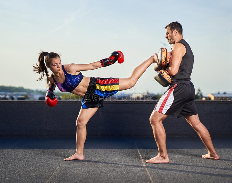 Young woman kickboxer in urban environment, training. Young women kickbox fighter training with her coach on the roof above the city royalty free stock image