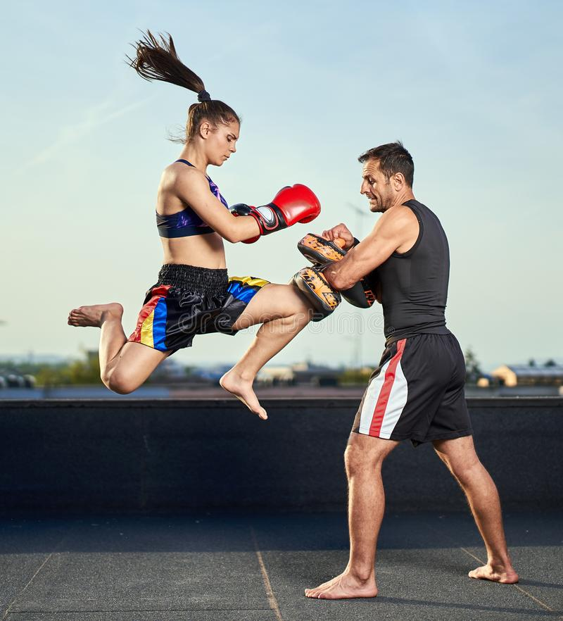 Young woman kickboxer in urban environment, training royalty free stock photos