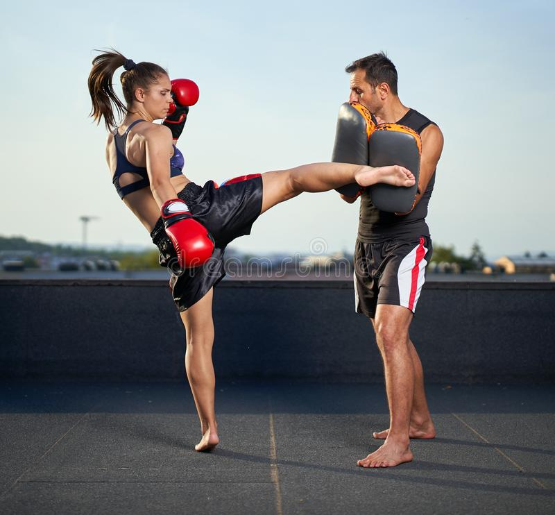 Young woman kickboxer in urban environment, training. Young women kickbox fighter training with her coach on the roof above the city stock image