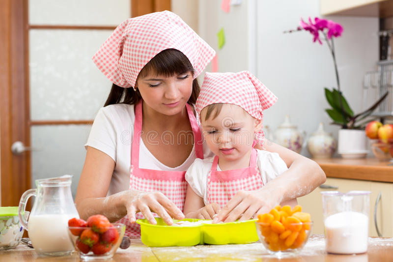 Young woman and kid daughter making berry fruit cake stock photos