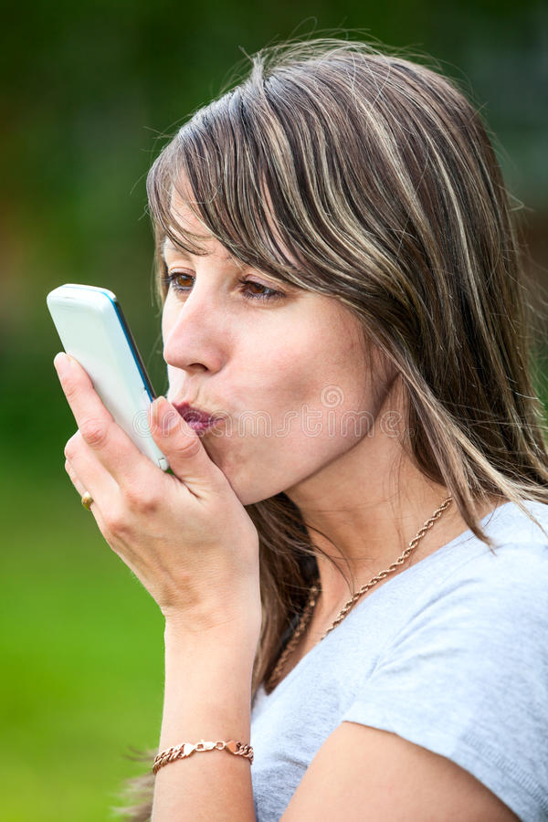 Young woman kissing cellphone. Caucasian young female kissing cell phone outdoor stock image