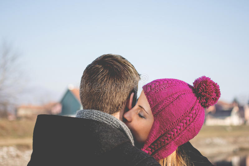 Young woman kissing her boyfriend's neck stock image