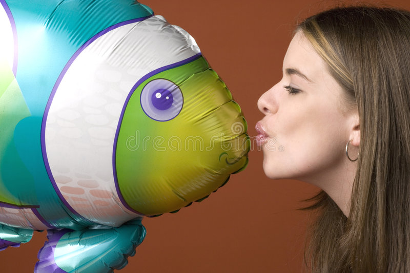 Young woman kissing an inflatable fish toy royalty free stock image