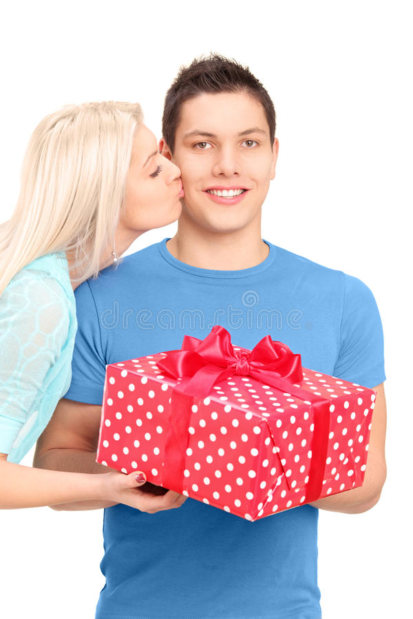 Young woman kissing a man with a present box royalty free stock photo