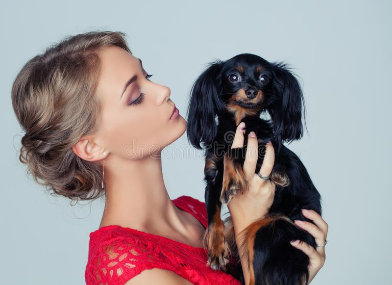 Young Woman Kissing Puppy on White Background stock photography