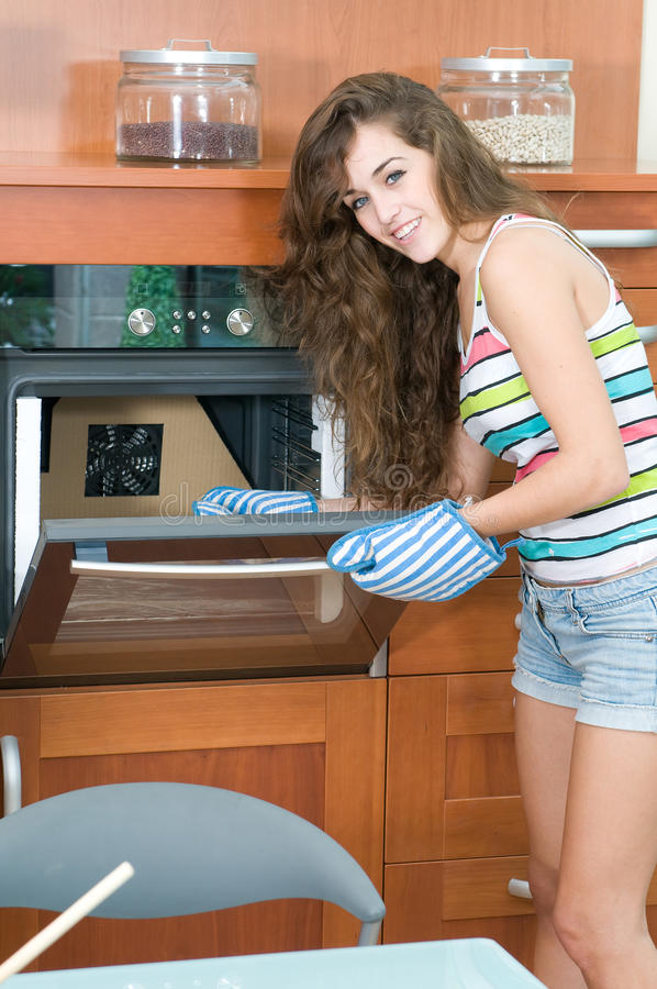 Young woman in the kitchen at the oven royalty free stock image