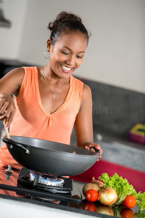 Young woman in the kitchen preparing food royalty free stock photos