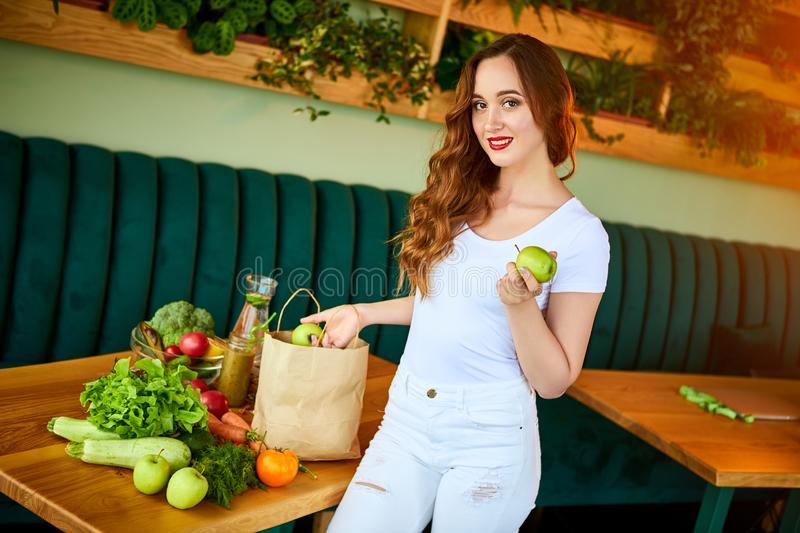 Young woman at kitchen taking out apple from grocery shopping paper bag with fruits and vegetables products stock image