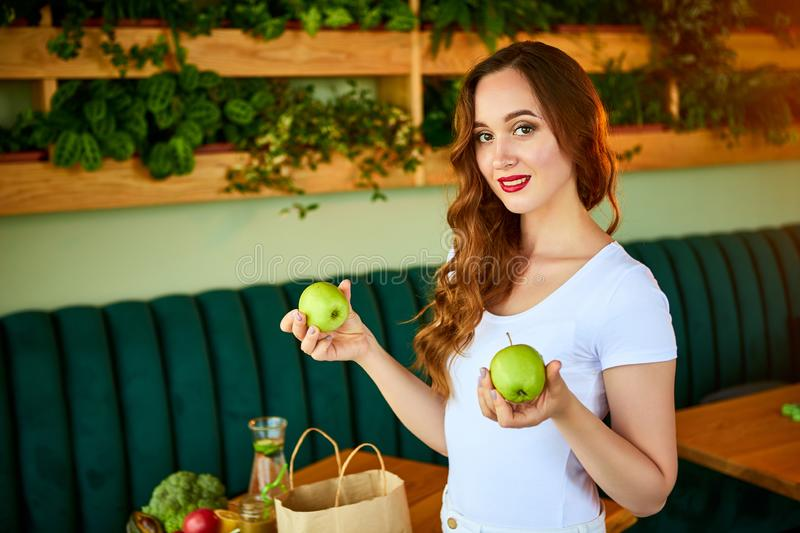 Young woman at kitchen taking out apple from grocery shopping paper bag with fruits and vegetables products royalty free stock image