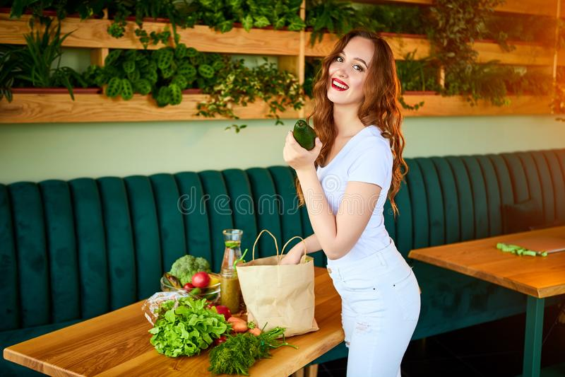 Young woman at kitchen taking out avocado from grocery shopping paper bag with fruits and vegetables products stock photos