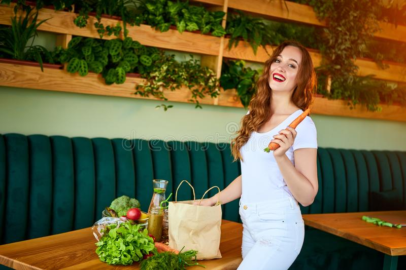 Young woman at kitchen taking out carrot from grocery shopping paper bag with fruits and vegetables products stock photography
