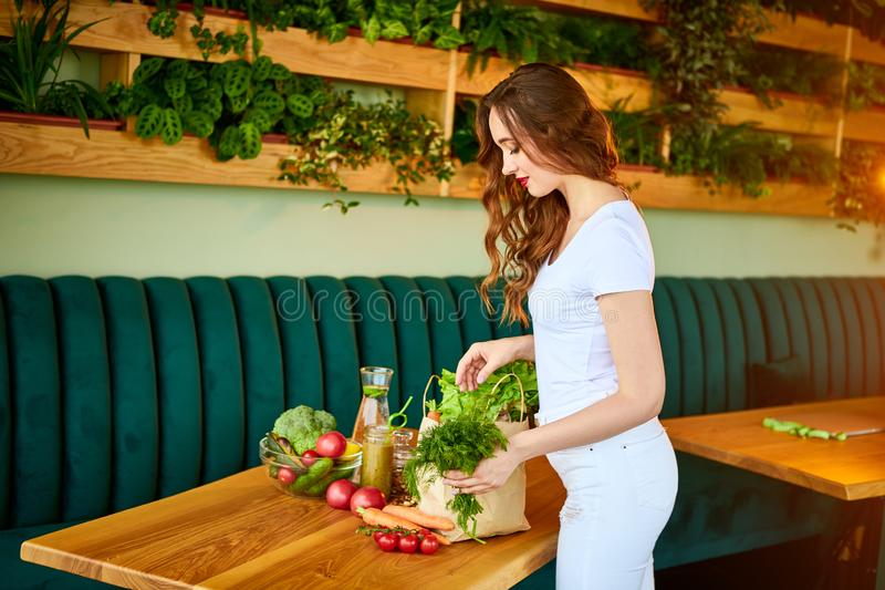 Young woman at kitchen taking out dill from grocery shopping paper bag with fruits and vegetables products royalty free stock photo